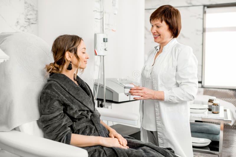 Doctor con el cliente de la mujer en un centro turístico médico foto de archivo libre de regalías