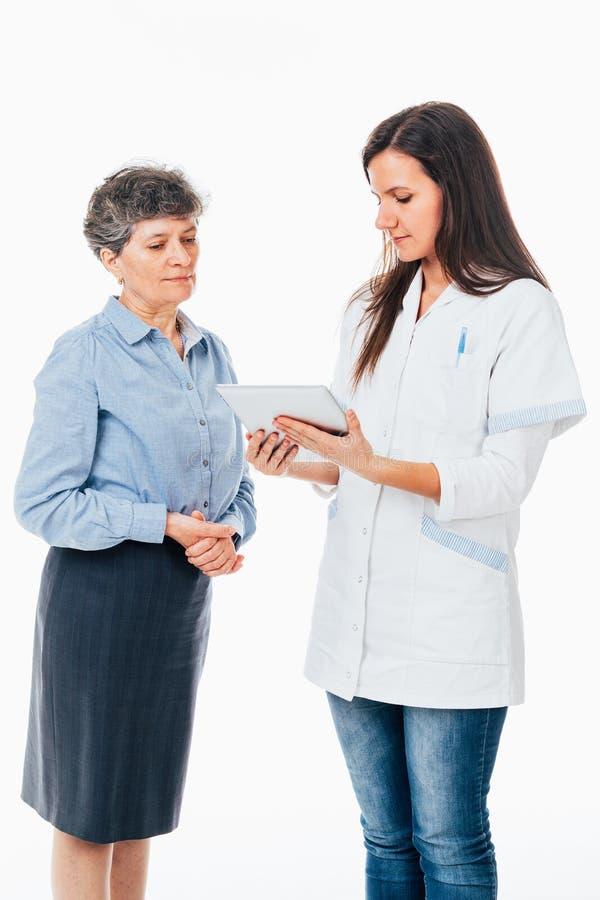 Doctor con el cojín que explica enfermedad al paciente foto de archivo