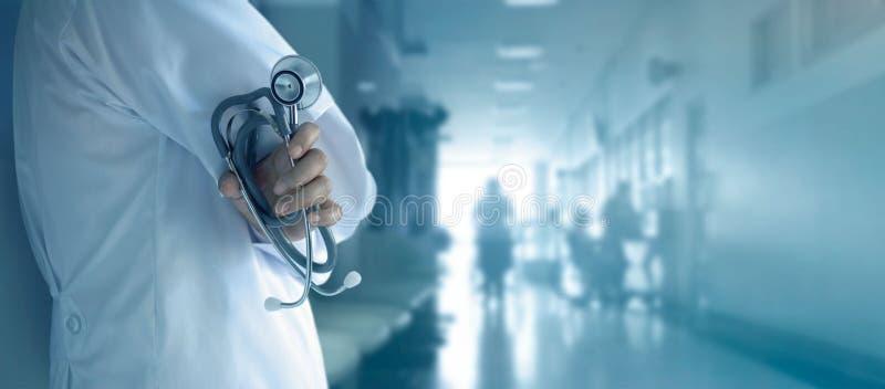 Doctor con el estetoscopio a disposición en fondo del hospital fotos de archivo libres de regalías
