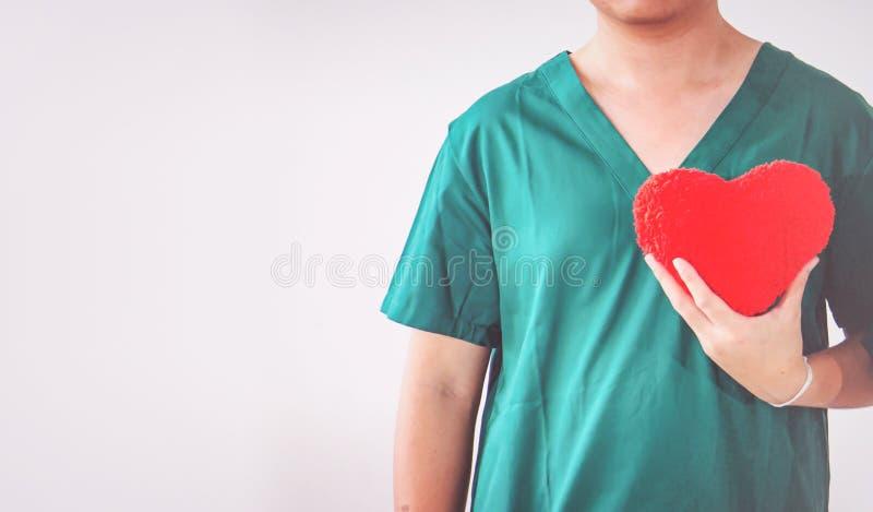 Doctor con el estetoscopio que examina el coraz?n rojo imagen de archivo libre de regalías