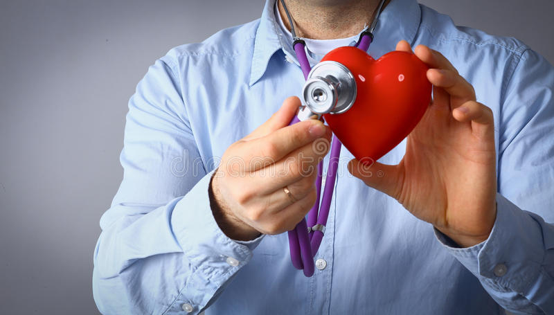 Doctor con el estetoscopio que examina el corazón rojo, aislado en el fondo blanco fotografía de archivo libre de regalías
