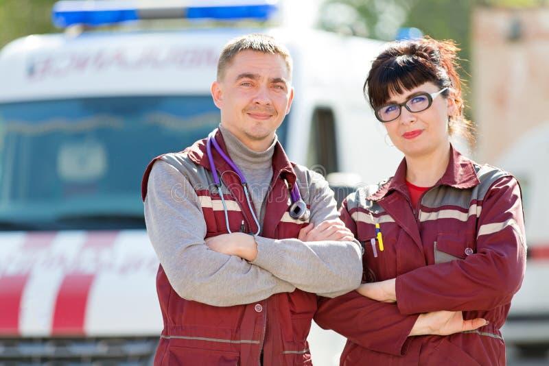 Doctor con el paramédico del colega en fondo del vehículo de la ambulancia imágenes de archivo libres de regalías