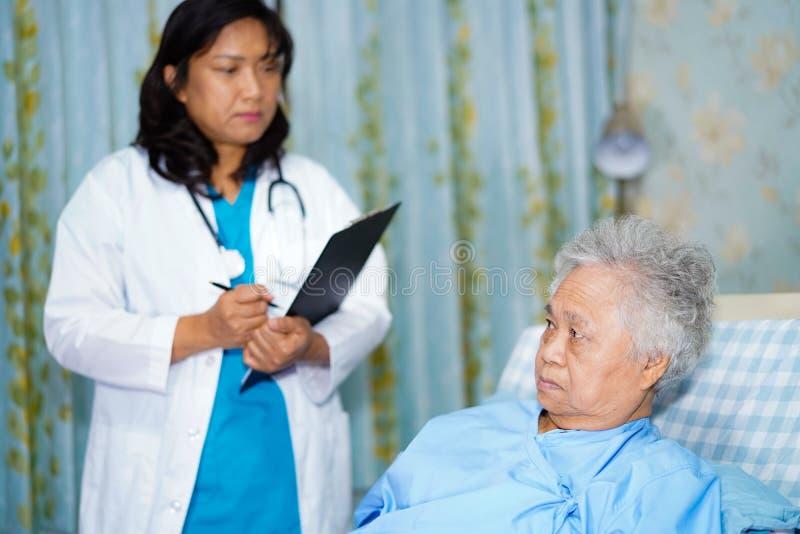 Doctor con el tablero para la diagnosis de la nota de pacientes en sala de hospital de cuidado imagen de archivo