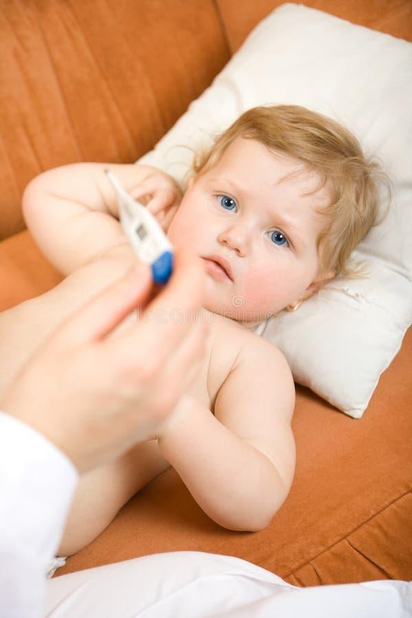 Doctor con el termómetro del bebé y de la lectura imagen de archivo libre de regalías