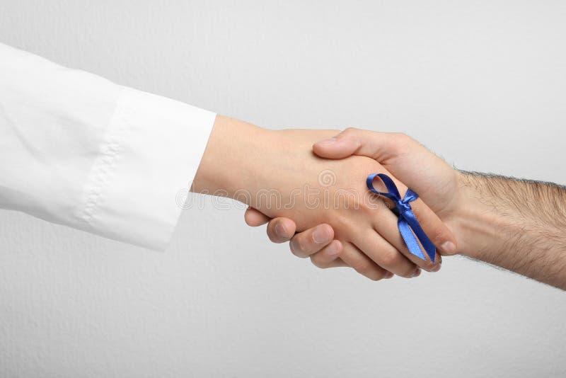 Doctor con la cinta azul en el finger y el paciente que llevan a cabo las manos contra fondo gris Símbolo de problemas médicos imagen de archivo