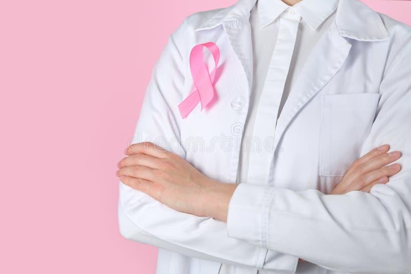 Doctor con la cinta rosada en el traje contra fondo del color Concepto de la conciencia del c?ncer de pecho fotos de archivo libres de regalías