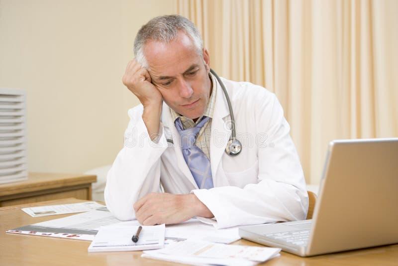 Doctor con la computadora portátil en la oficina del doctor fotos de archivo