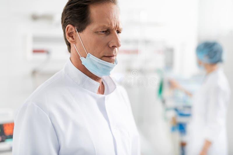 Doctor con la máscara protectora en la barbilla que se coloca en sitio de hospital imagen de archivo