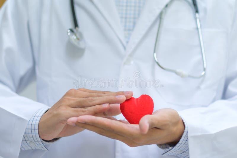 Doctor con la mano del estetoscopio que lleva a cabo forma roja del corazón en el hospital foto de archivo