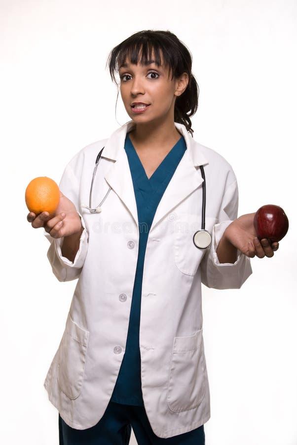 Doctor con la manzana y la naranja foto de archivo