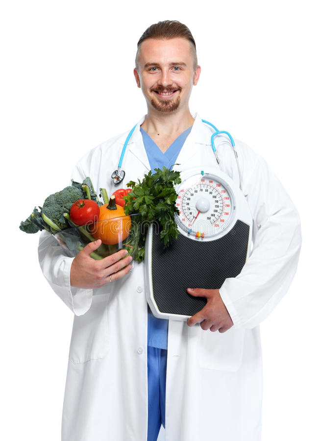 Doctor con las verduras y las escalas del cuerpo fotografía de archivo