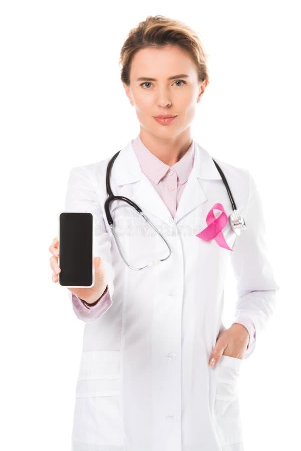 doctor con smartphone rosado de la tenencia de la cinta con la pantalla en blanco y la mirada de la cámara aislada en blanco, con imagen de archivo