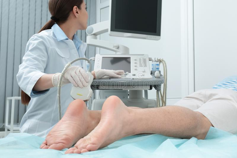 Doctor conducting ultrasound examination of patient`s foot. In clinic stock image