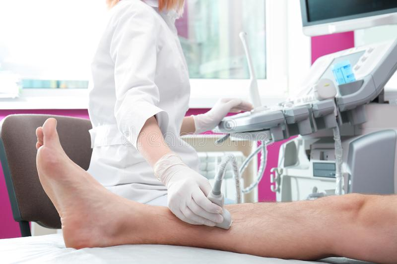 Doctor conducting ultrasound examination of patient`s leg in clinic. Closeup stock photo