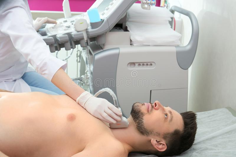 Doctor conducting ultrasound examination of thyroid gland. In clinic stock photography