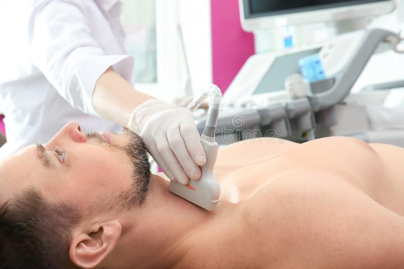 Doctor conducting ultrasound examination of thyroid gland. In clinic royalty free stock photography