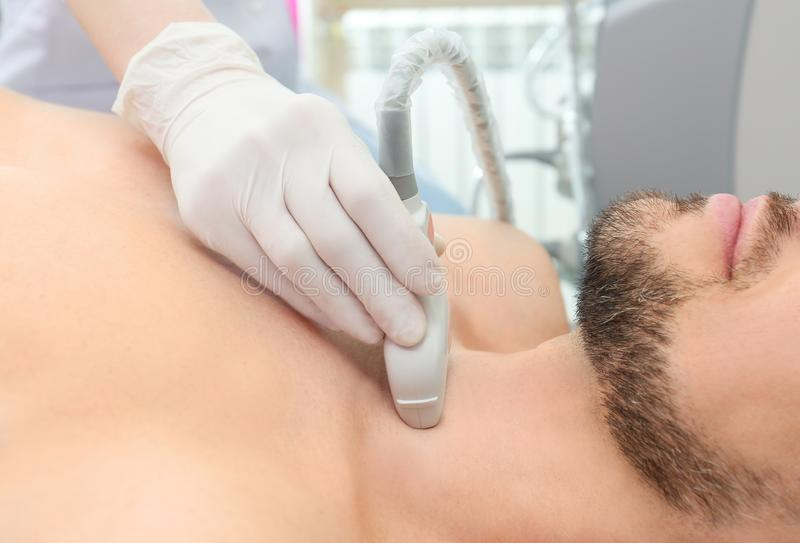 Doctor conducting ultrasound examination of thyroid gland. In clinic stock photos
