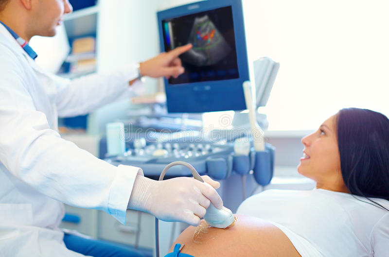 Doctor conducting the ultrasound procedure to pregnant woman. Doctor conducting the ultrasound procedure to pretty pregnant woman stock photo