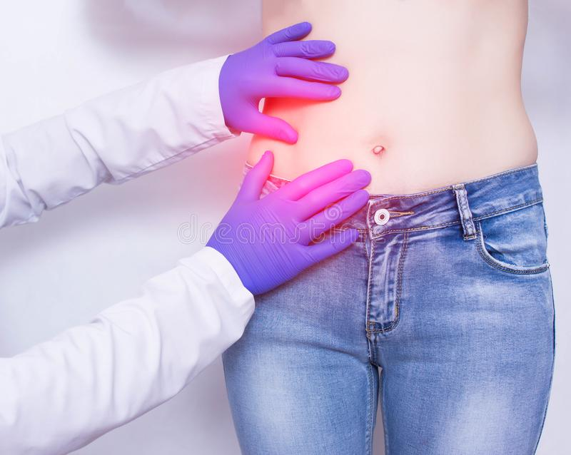 The doctor conducts a visual inspection and palpation of the patient s abdomen on suspicion of acute apendicitis and inflammation stock photo