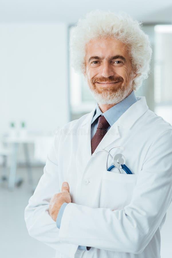 Doctor confiado que presenta con los brazos doblados foto de archivo libre de regalías