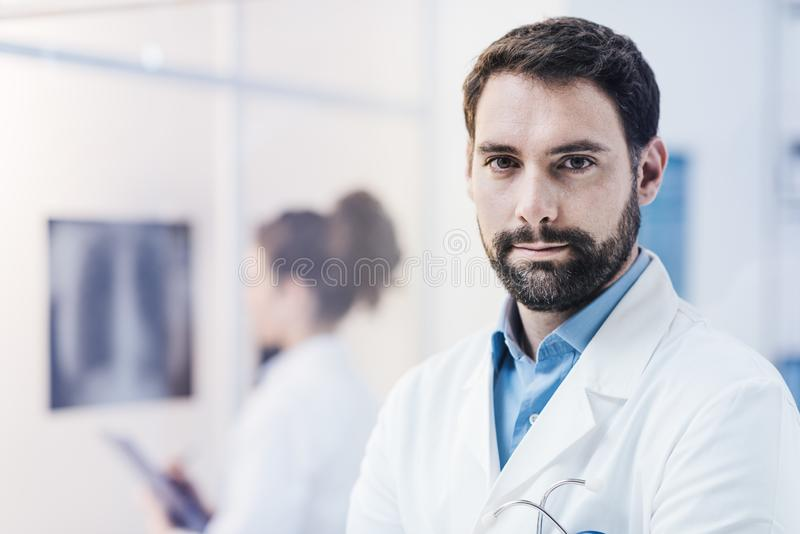 Doctor confiado que presenta en la oficina fotografía de archivo
