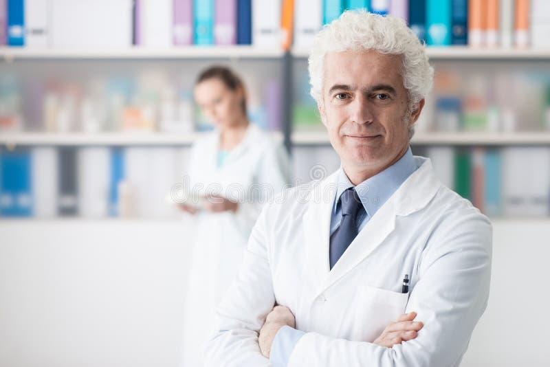 Doctor confiado que presenta en su oficina fotografía de archivo