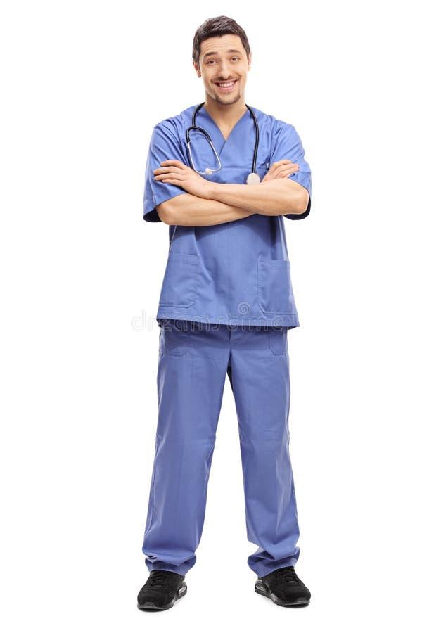 Doctor confiado que presenta en un uniforme azul foto de archivo