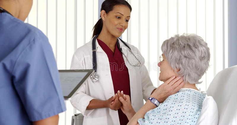 Doctor consoling elderly woman patient in hospital bed stock photos