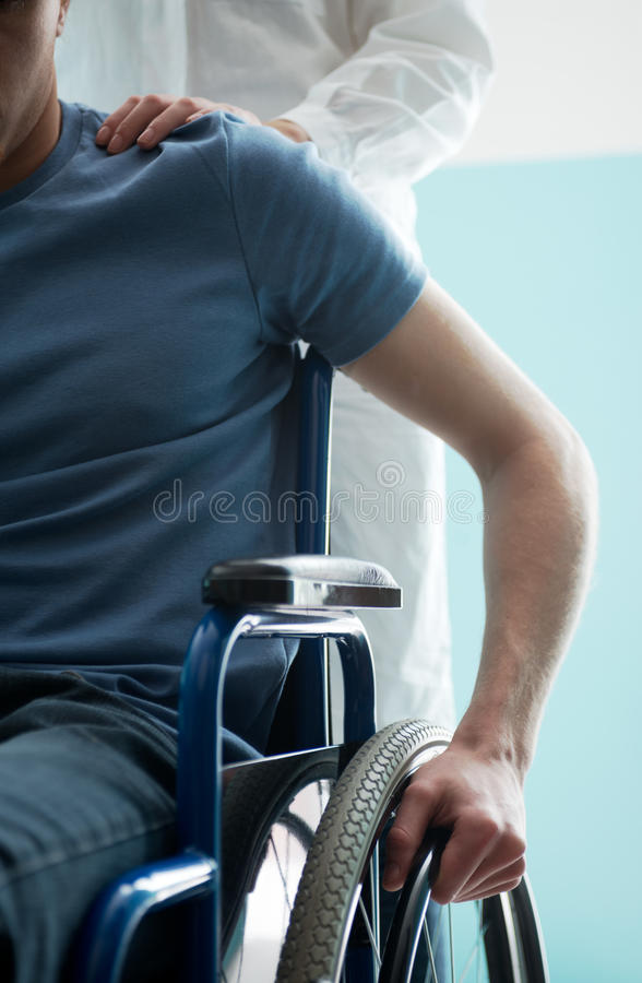 Doctor consoling young man sitting in wheelchair royalty free stock images