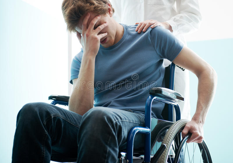 Doctor consoling young man sitting in wheelchair stock photos