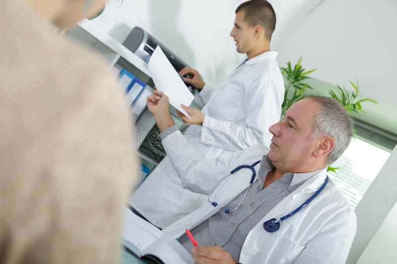 Doctor consultation with assistant in background stock photography