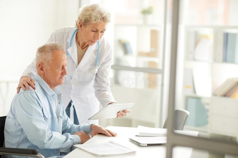Doctor Consulting Elderly Man. Portrait of female doctor using digital tablet while consulting elderly man, copy space royalty free stock photo