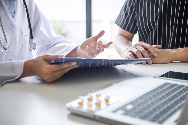 Doctor consulting patient discussing something symptom of disease and recommend treatment methods, presenting results on report royalty free stock images