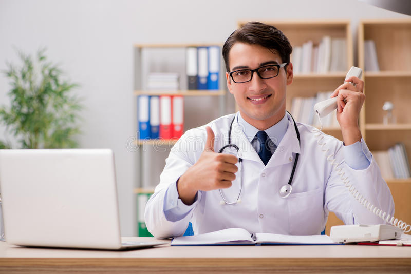 The doctor consulting patient over the phone. Doctor consulting patient over the phone stock photo
