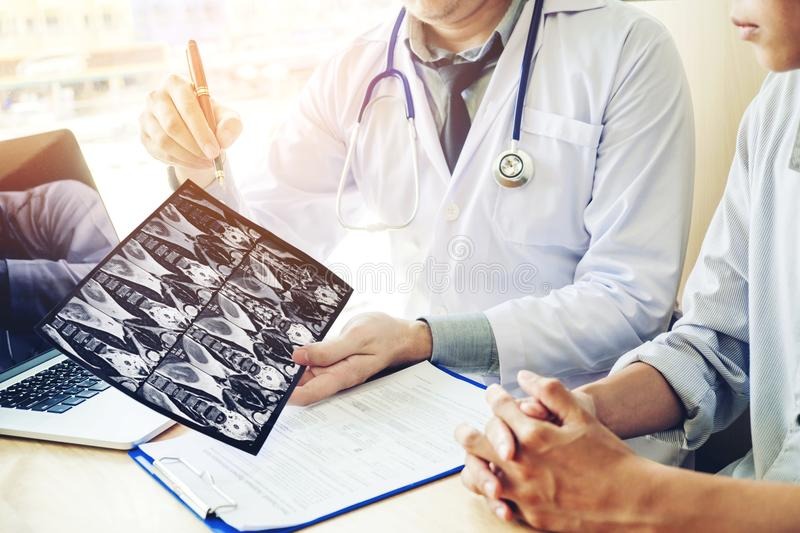 Doctor consulting with patient presenting results on x-ray film royalty free stock images