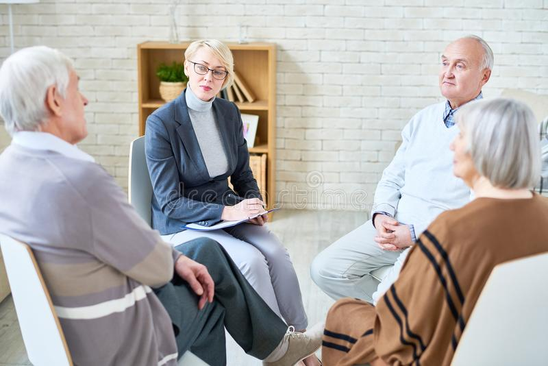 Doctor consulting senior people in nursing home stock photo
