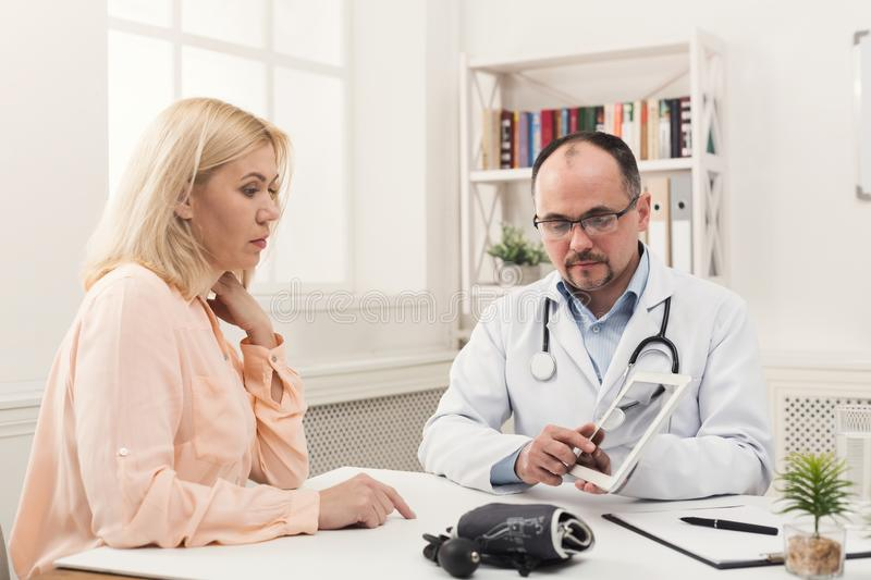 Doctor consulting woman in hospital stock image