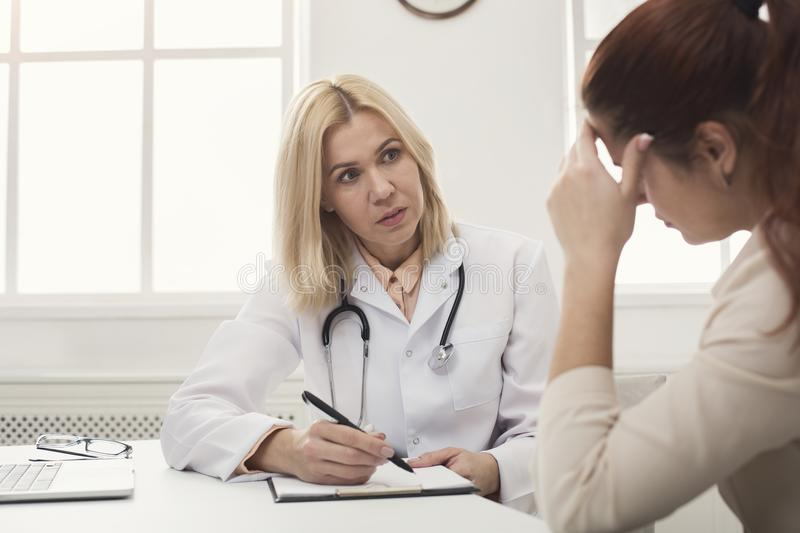Doctor consulting woman in hospital stock photo