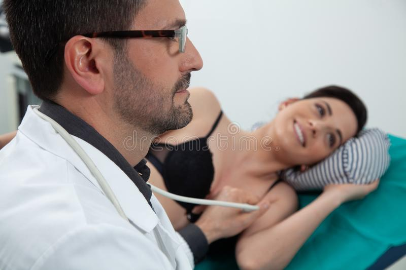 Doctor controling his female patient using an ecography. A dark hair doctor listening to his female patient with a ultrasound ecography in a medical room using a royalty free stock photography