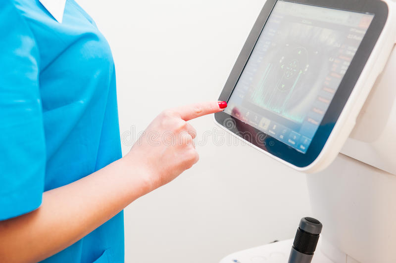 Doctor controls instrument exploring patients eye in ophthalmology clinic, Auto-Ref-Keratometer. Close up, selective focus. Doctor controls instrument exploring stock image