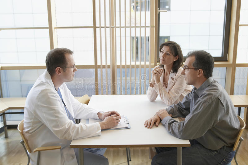 Doctor In Conversation With A Couple At Desk stock photos