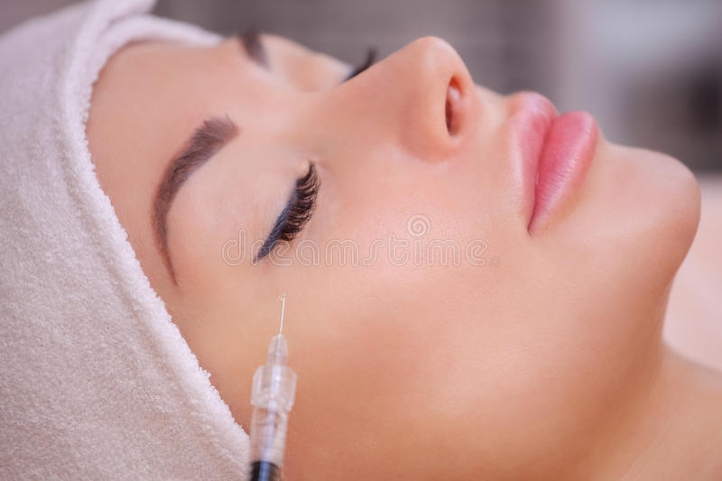 The doctor cosmetologist makes the Botulinotoxin injection procedure for tightening and smoothing wrinkles on the face stock image