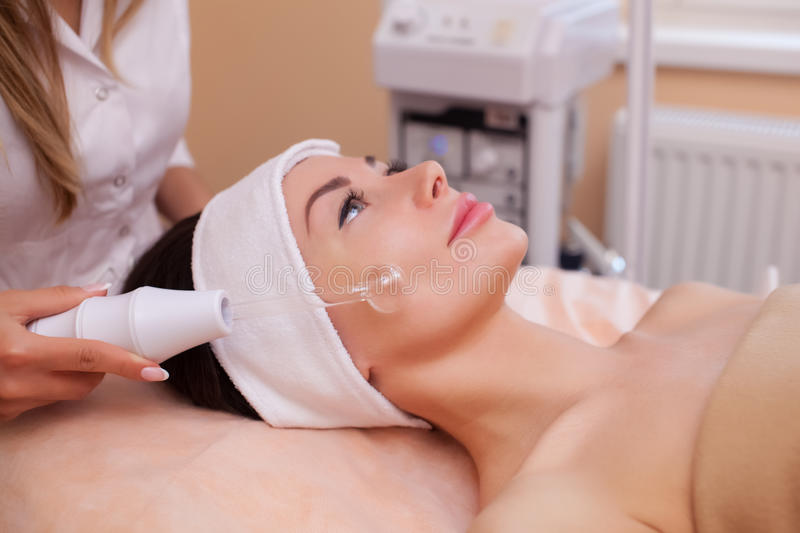 The doctor-cosmetologist makes the procedure Microcurrent therapy of the facial skin of a beautiful, young woman royalty free stock images