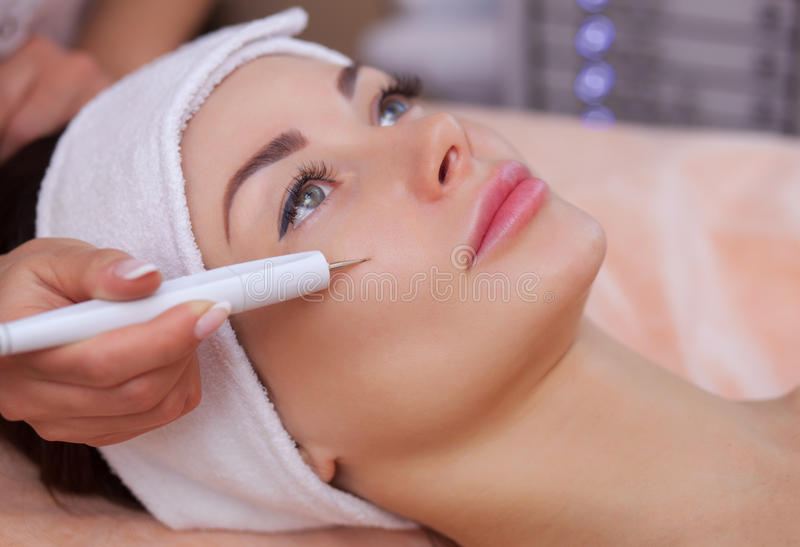 The doctor-cosmetologist makes the procedure treatment of Couperose of the facial skin stock photo