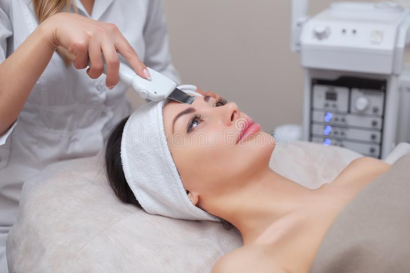 The doctor-cosmetologist makes the ultrasound cleaning procedure of the facial skin of a beautiful, young woman in a beauty salon royalty free stock image