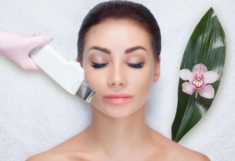 The doctor-cosmetologist makes the ultrasound cleaning procedure of the facial skin of a beautiful, young woman in a beauty salon. stock photo