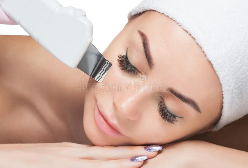 The doctor-cosmetologist makes the ultrasound cleaning procedure of the facial skin of a beautiful, young woman in a beauty salon stock image
