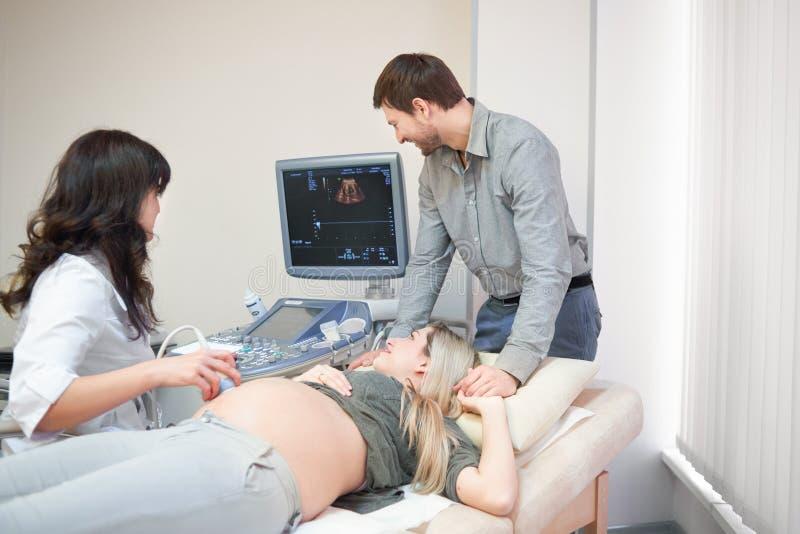Doctor de asistencia cariñoso de los pares para el procedu del sonido del embarazo ultra imagen de archivo