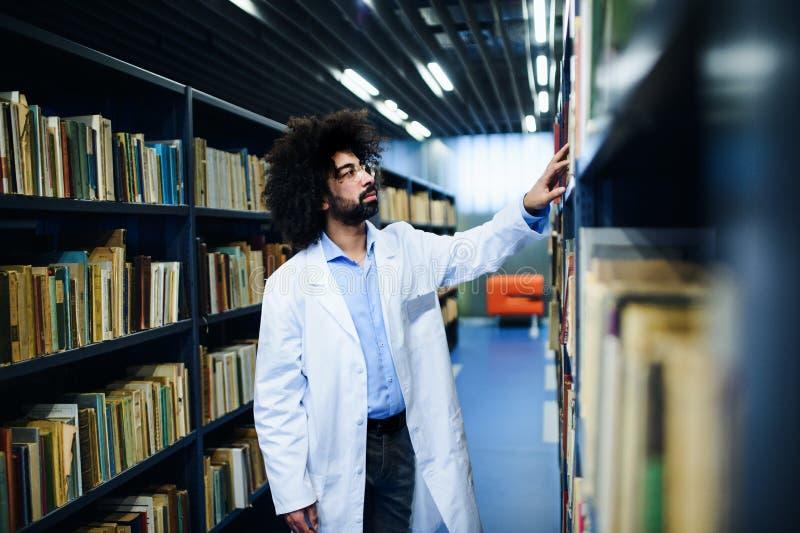 Doctor in de bibliotheek, op zoek naar een boek op de plank royalty-vrije stock fotografie