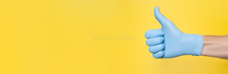 Doctor in de blauw Latex-handschoen met duim omhoog Gele achtergrond Kopieerruimte royalty-vrije stock afbeeldingen
